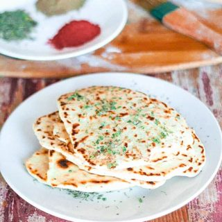 stack of vegan naan on a white plate sitting on top of a wood table