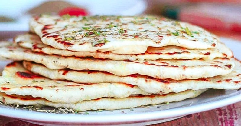 side view of stack of vegan naan no yeast on a white plate
