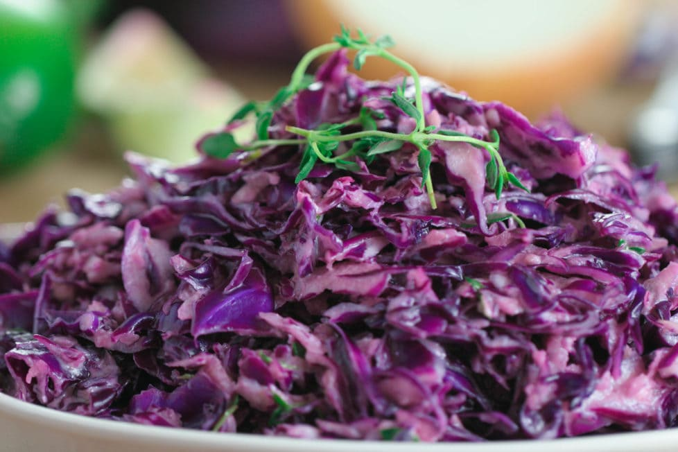 A close up of a purple cabbage slaw on a white plate