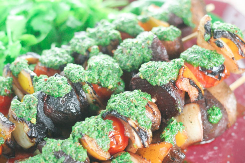A close up of a plate of veggie skewers with basil chimichurri sauce