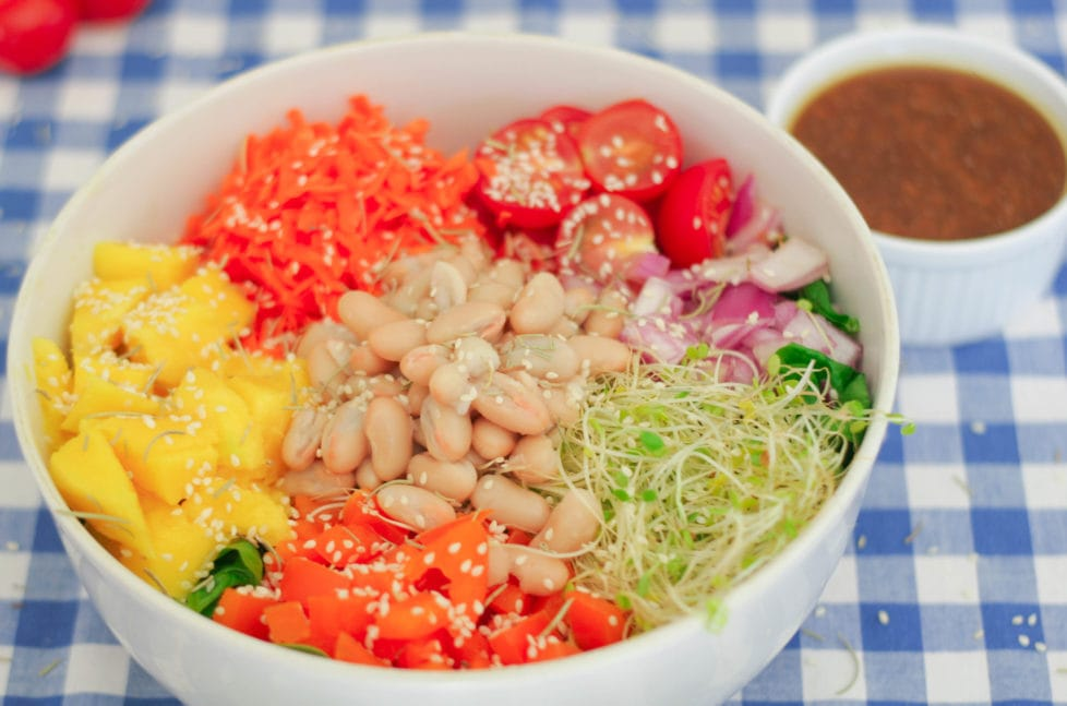 A white bowl filled with salad on a blue and white checkered table cloth