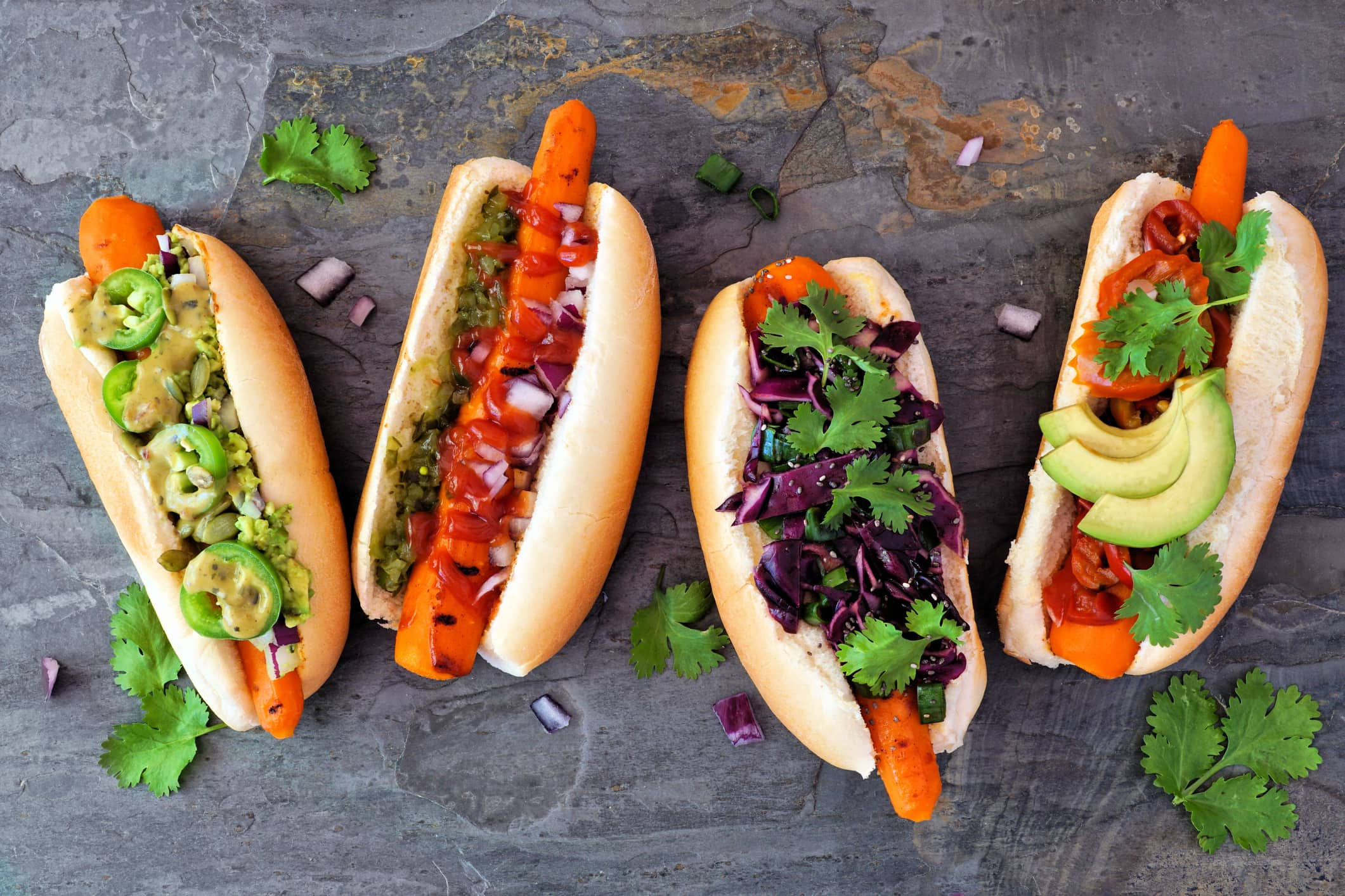 four carrot dogs on a slate table with different toppings