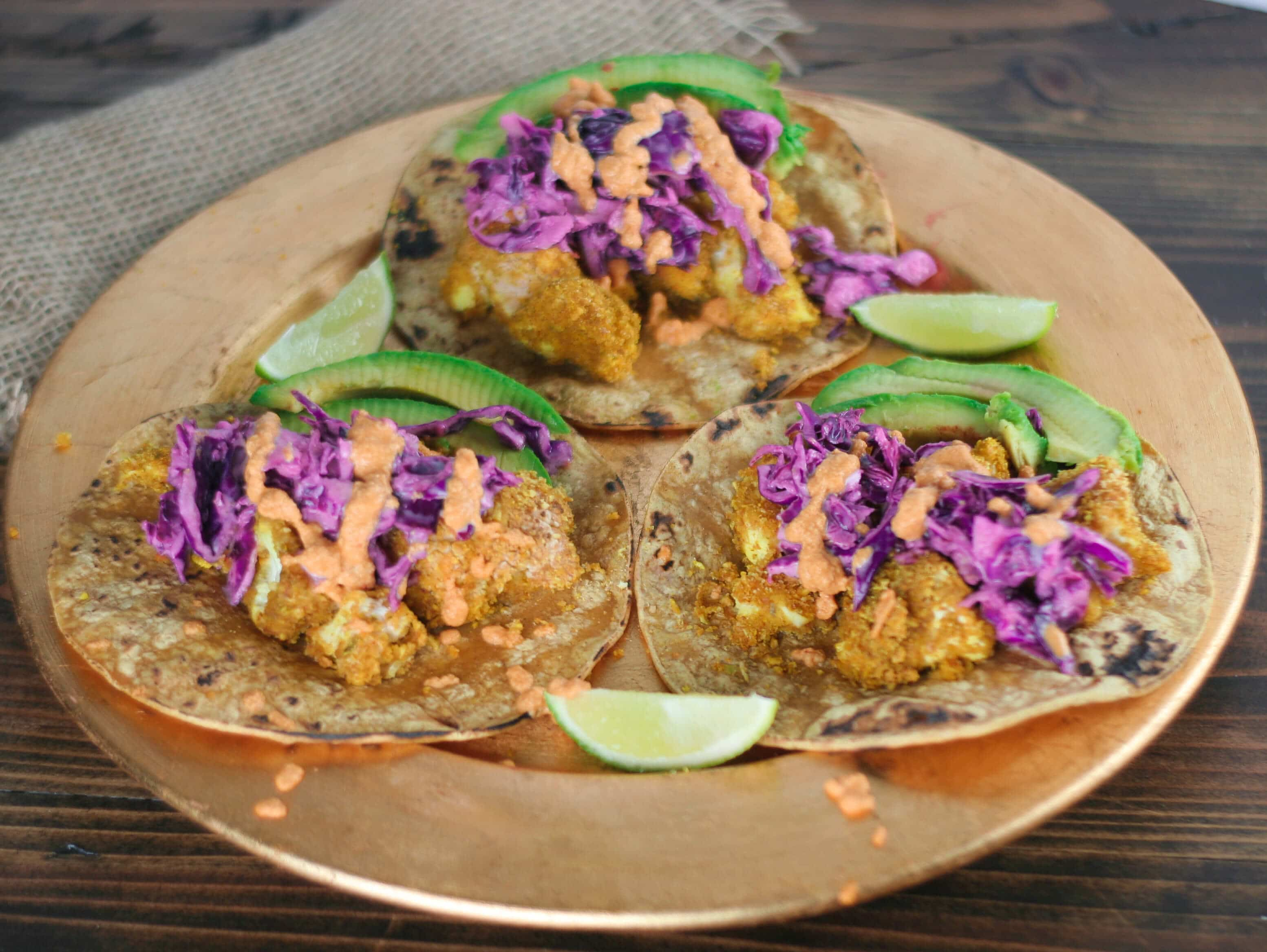 three tacos on a gold plate with cabbage and lime