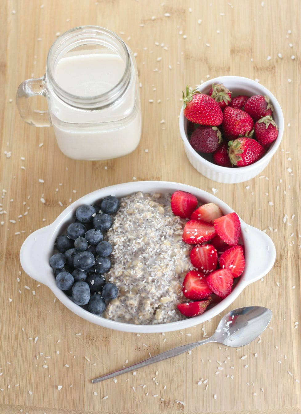 A bowl of overnight oats on a wooden table with berries and plant based milk