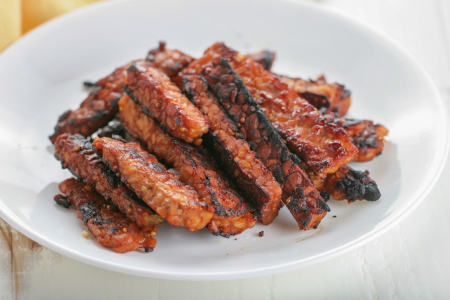 A white plate full of Tempeh bacon