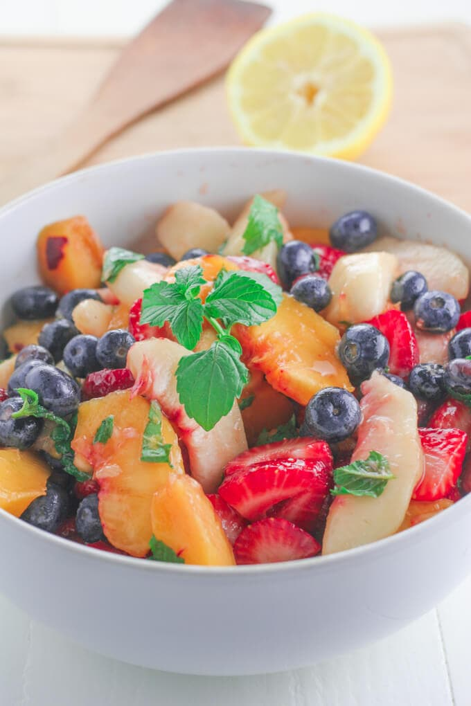 A bowl of fruit in a white bowl with mint on top