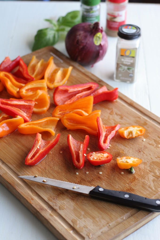 A knife sitting on top of a wooden cutting board, with Mini Peppers being sliced