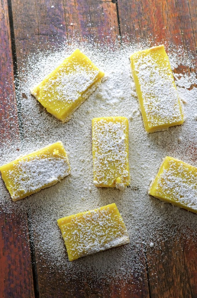 vegan lemon bars on a wood table sprinkled with powdered sugar