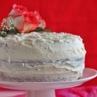 A whole frosted vegan cake on a cake plate with roses on top and a red background