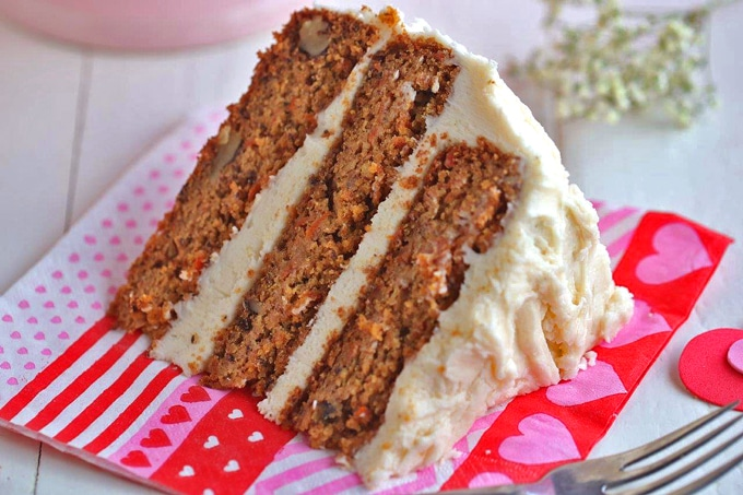 A slice of vegan carrot cake sitting on top of a paper plate