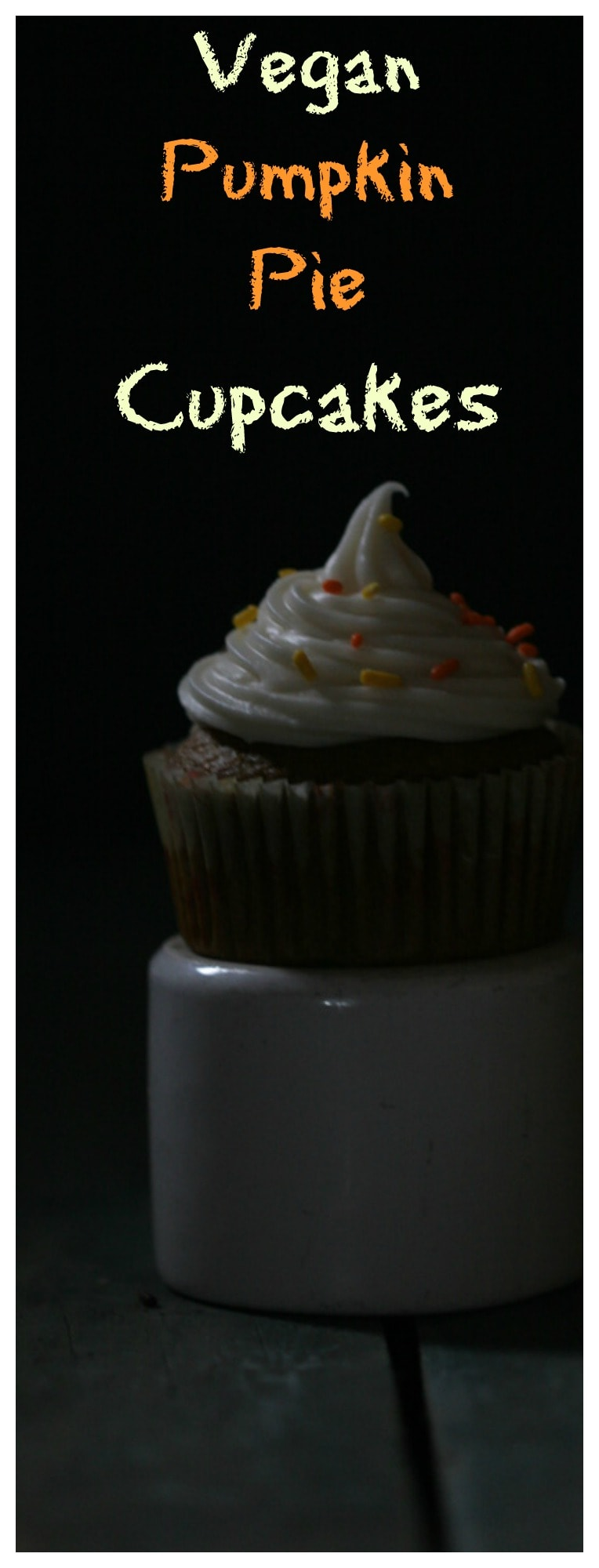 a dark picture of a cupcake with frosting and sprinkles
