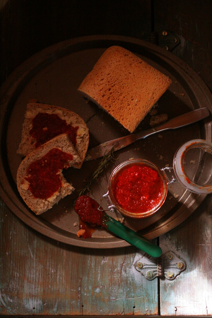 An overhead shot of three tomato jam with a loaf of bread and a couple slices taken out