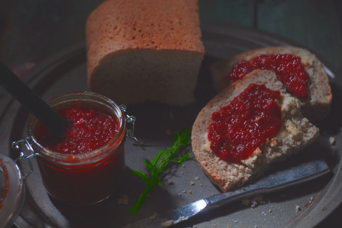 A close up of a three tomato jam with a slice of bread