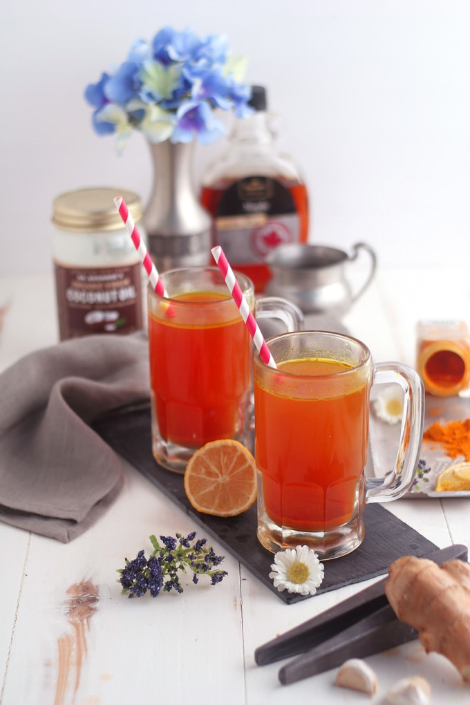 glasses of turmeric tonic surrounded by ingredients to make the recipe