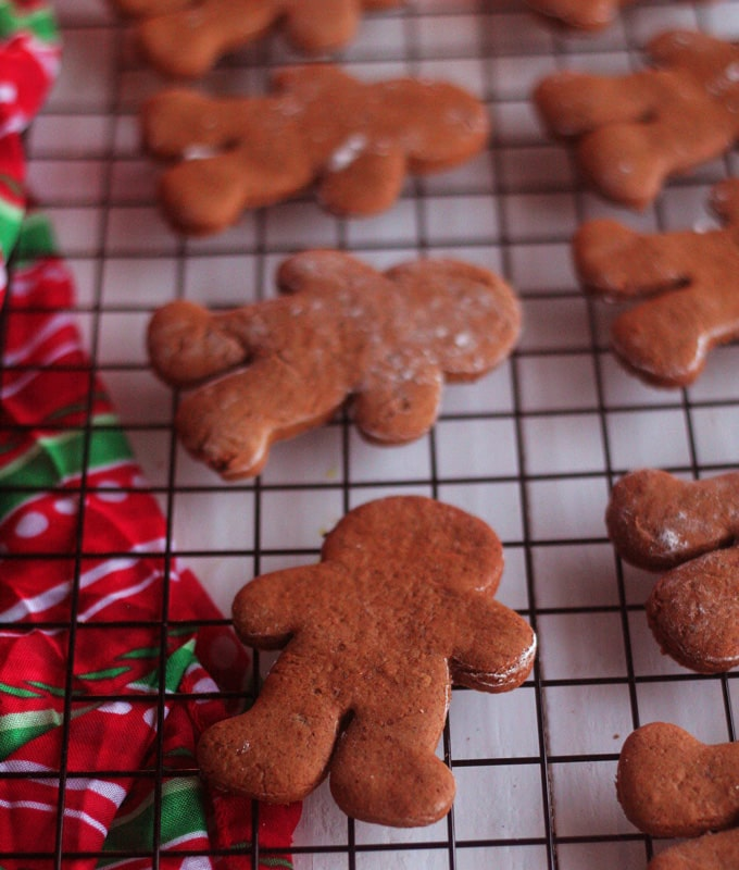 A group of gingerbread men on a cooling rack before being decorated