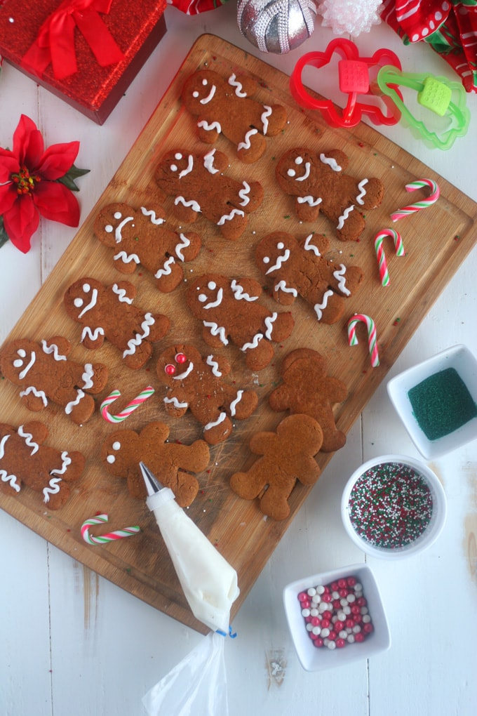 A cutting board with a bunch of gingerbread men on it with a person decorating one of them
