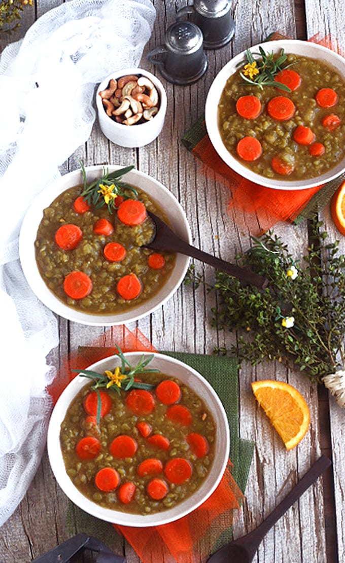 three bowls of split pea soup on a wooden table