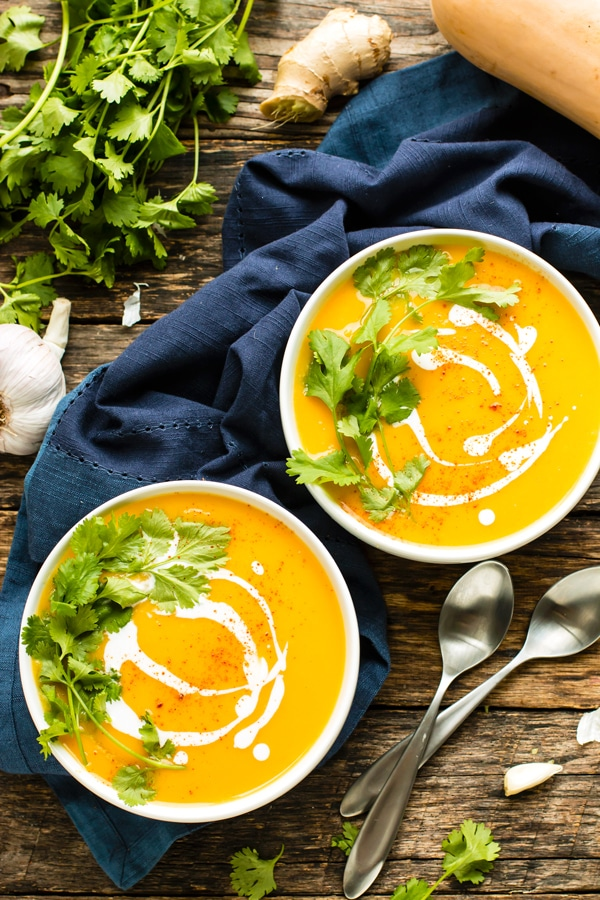 two bowls of butternut squash soup on a wood table