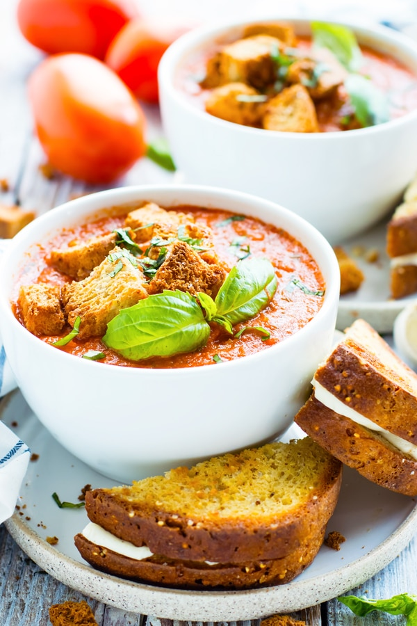 A bowl of tomato basil soup sitting on a table