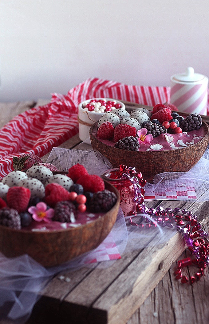 two bowls of berry smoothies on wood table