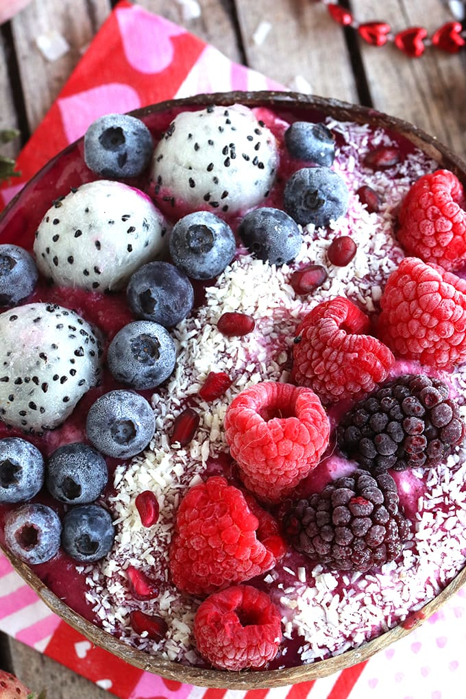 A close up berries and dragonfruit on top of smoothie