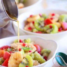 A close up someone pouring dressing on a bowl of fruit salad