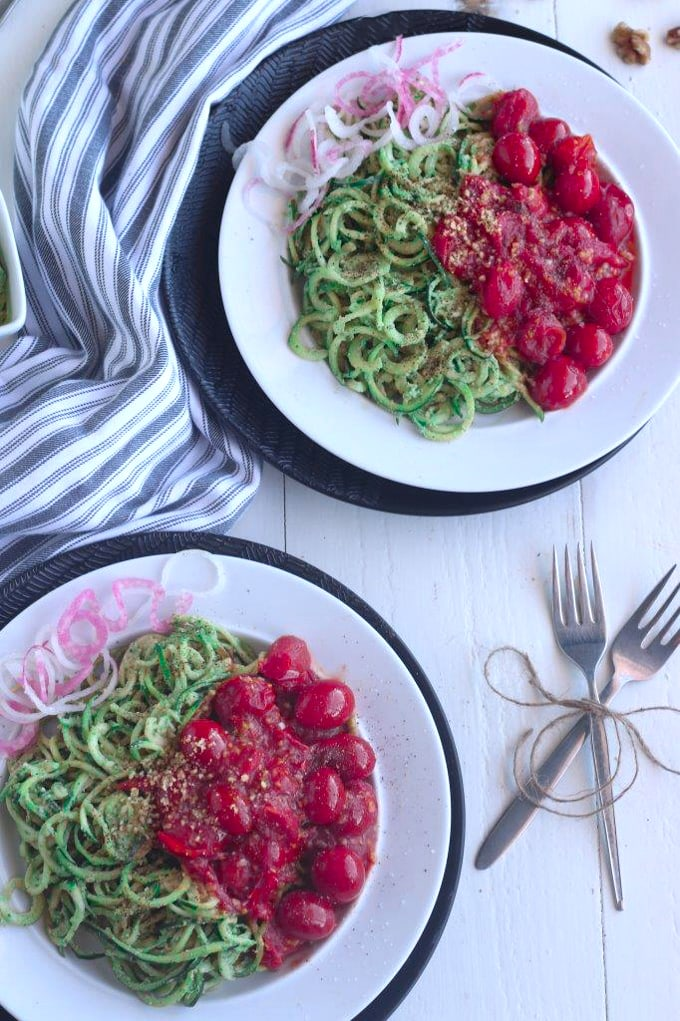 A closeup of two plates of pesto zoodles