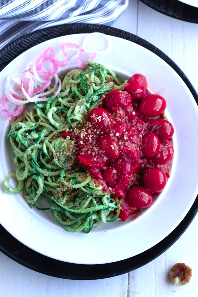A bowl of zucchini noodles on a plate, with tomatoes