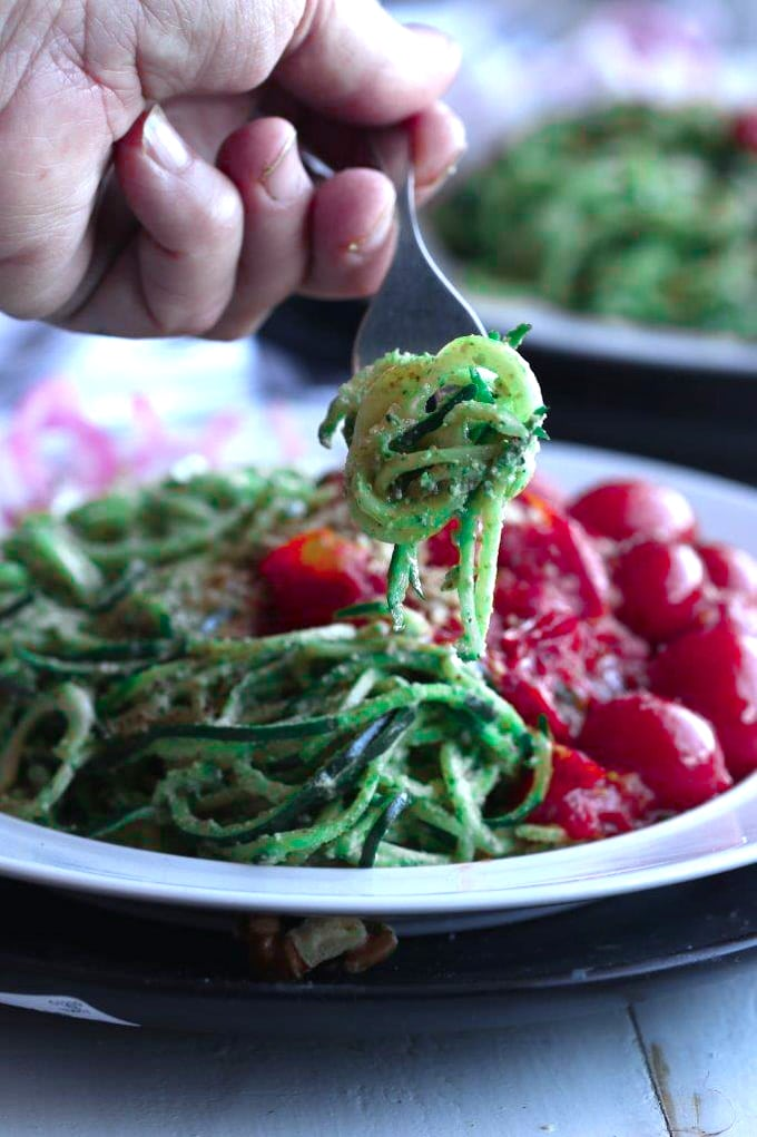 A close up of a person holding a forkful of zoodles