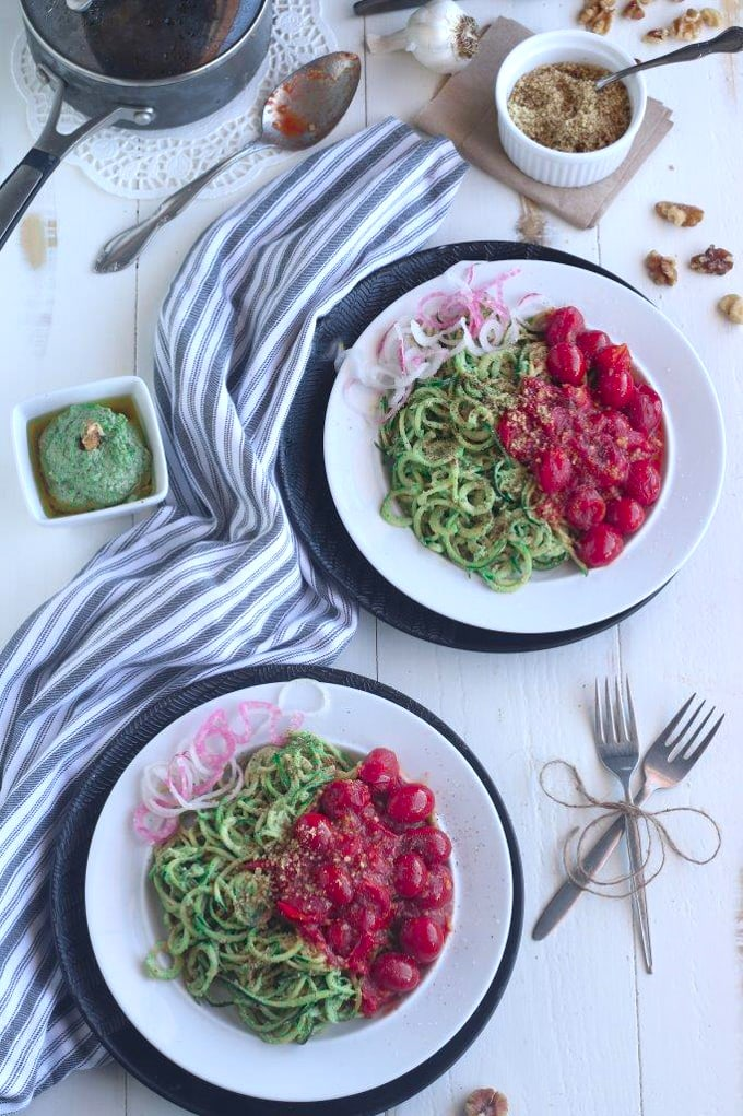 overhead shot of two white plates of zoodles on a white wooden table
