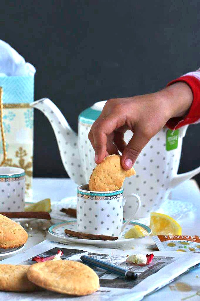 A person dunking a biscuit into cup of tea with tea pot in background