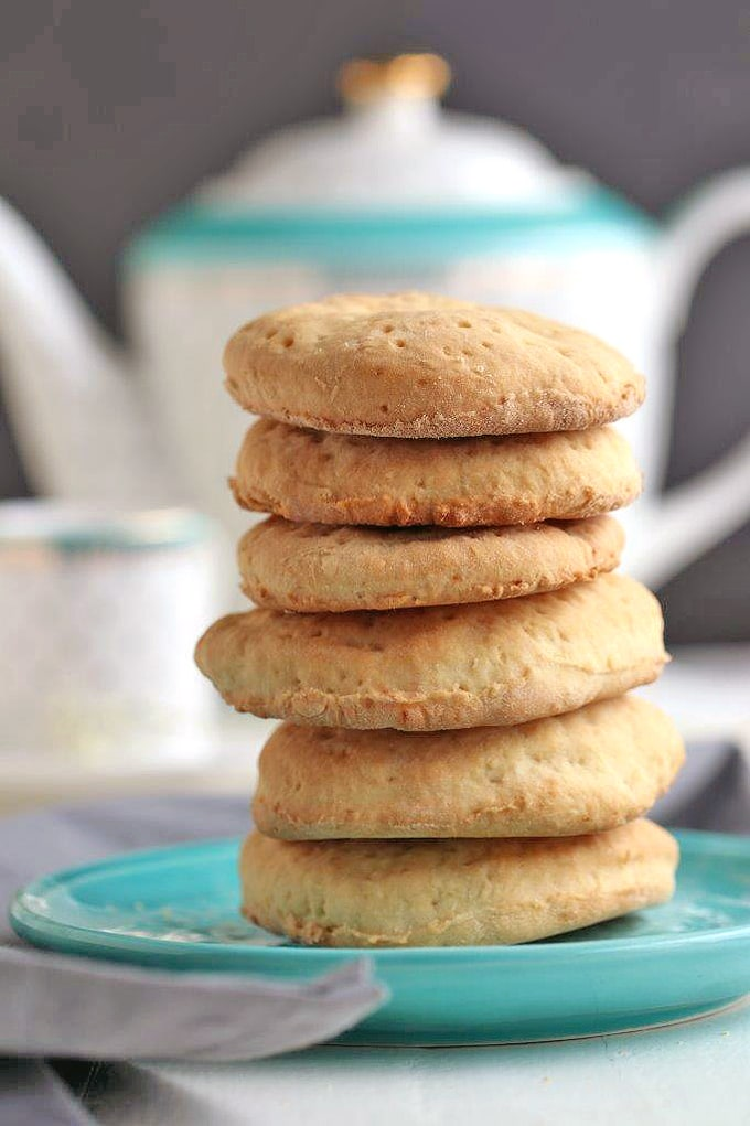 A stack of tea biscuits pancakes on a light blue plate with tea pot in background