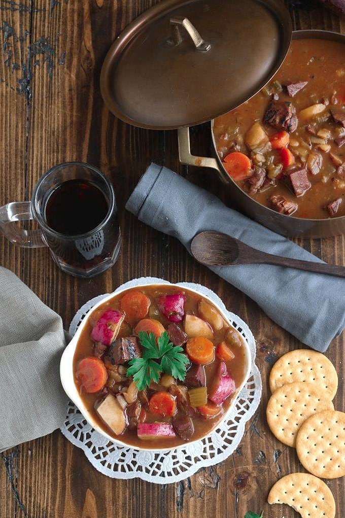 A white bowl of stew sitting on top of a wooden table, with glass of Guinness