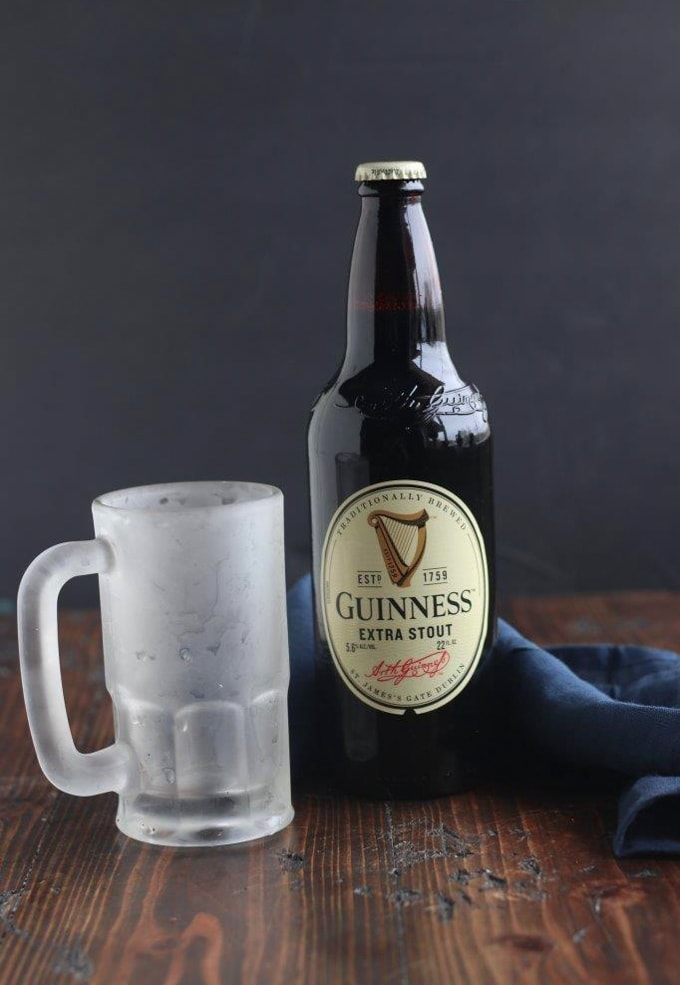 A glass bottle of Guinness next to an icy mug pint