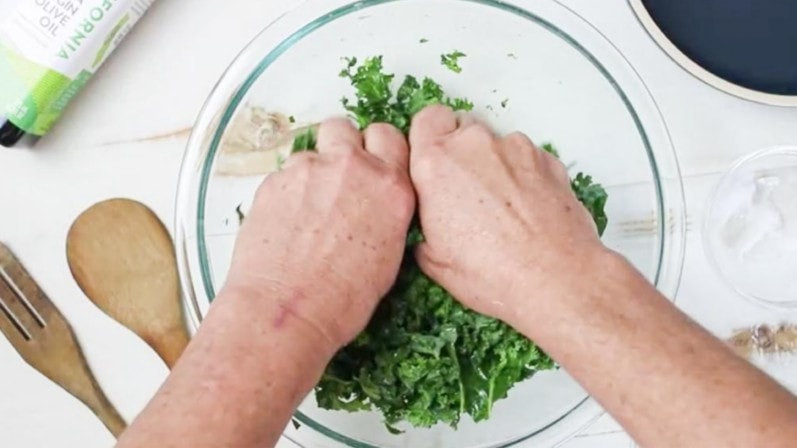 hands massaging kale in clear bowl on white wood table