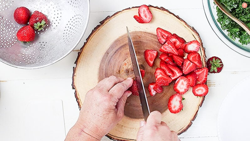 hands slicing strawberries with knife on wooden cutting board