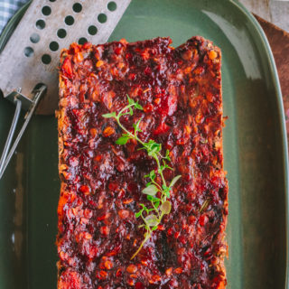 overhead shot of Vegan Lentil Loaf on a green platter topped with red sauce and rosemary