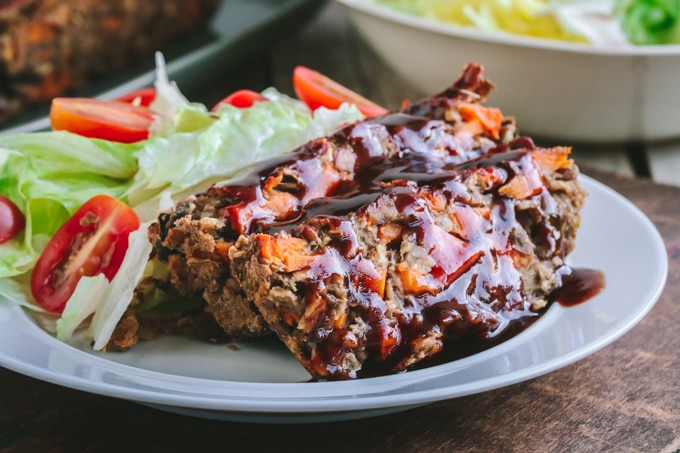 Two Slices of Vegan Lentil Loaf on White Plate with Side Salad
