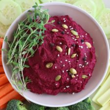 Roasted Beet Hummus in Beige Bowl with Assorted Vegetables
