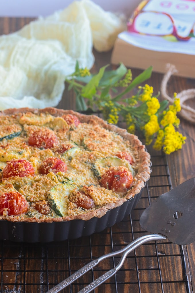A tomato zucchini tart in a pie tin on a wooden table