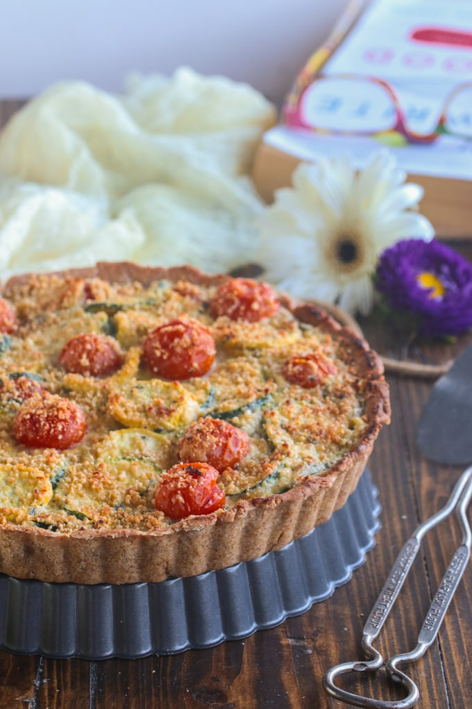 vegan tomato zucchini tart on a wooden table with flowers in background