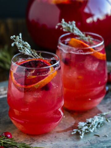 two glasses of cranberry spritzers on a table with candied rosemary