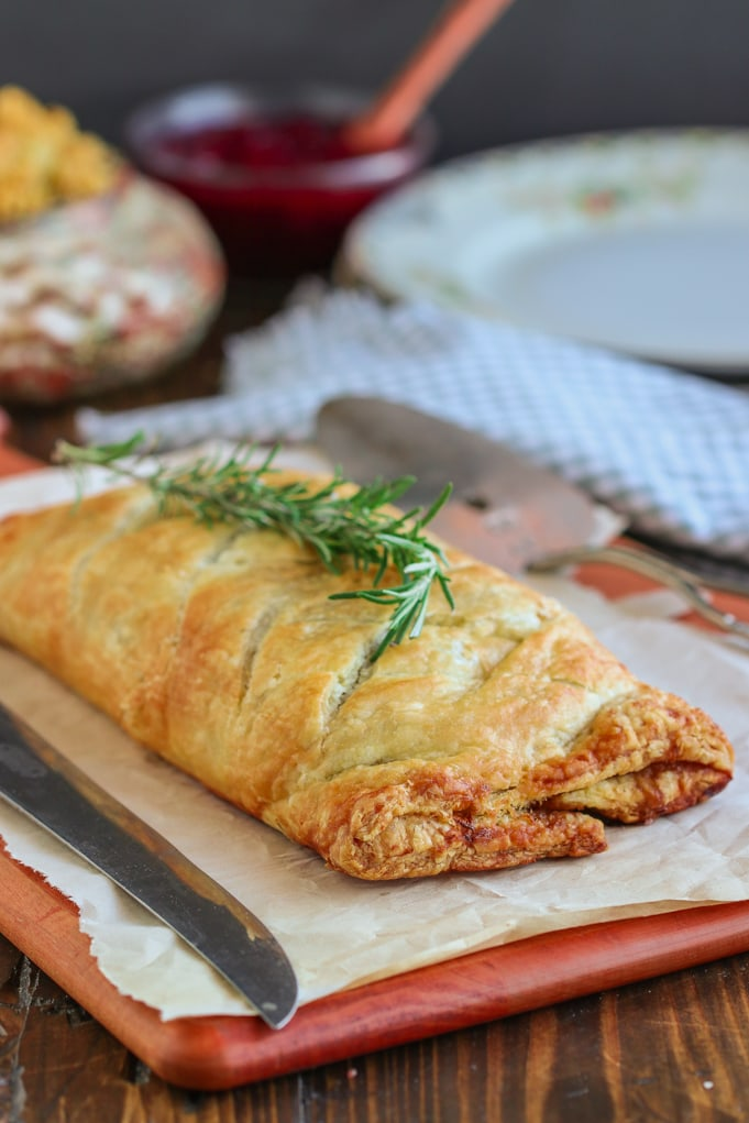 vegan mushroom wellington on cutting board with cranberries and stuffing on wooden table