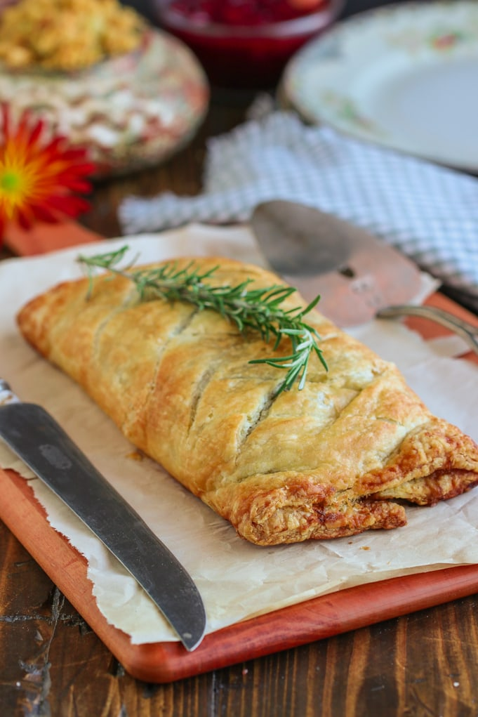 A whole mushroom wellington sitting on top of a wooden cutting board with Sweet potato