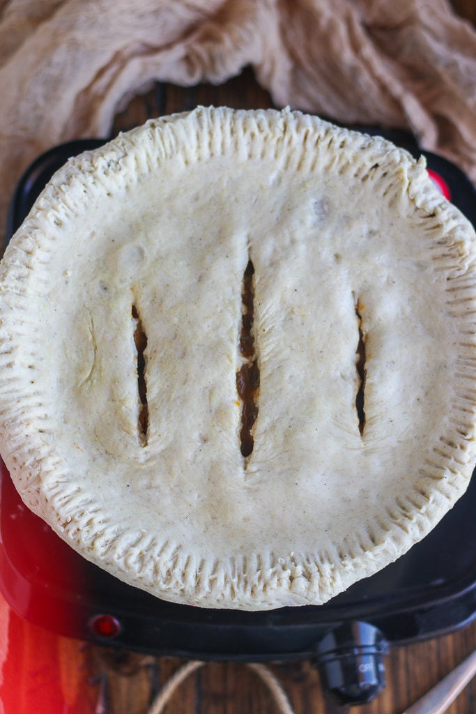uncooked pot pie with knife slicing's in top crust sitting on wooden table