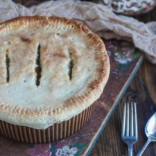A pot pie sitting on a wooden cutting board