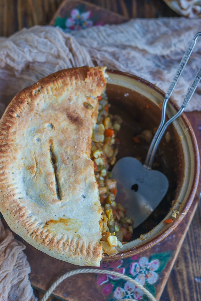 A casserole dish of half of a pot pie with a big spoon in it