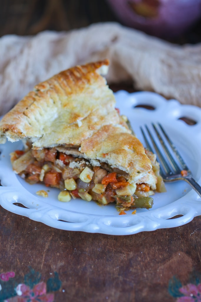 single slice of vegan pot pie on white plate with scalloped edges