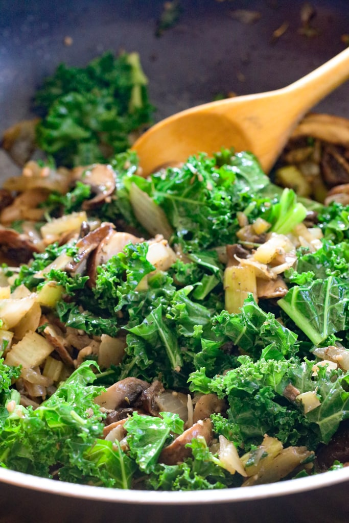 a person stiffing a skillet of kale, mushrooms and onions for stuffing