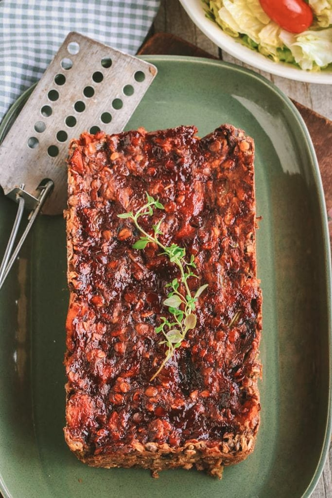 A plate of lentil loaf with rosemary on top